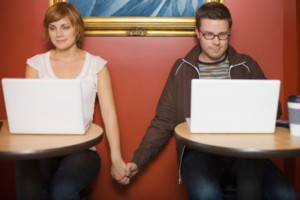 1208_couple-looking-at-computers-holding-hands_sm