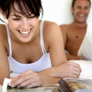 Young couple in bed, woman laughing with magazine